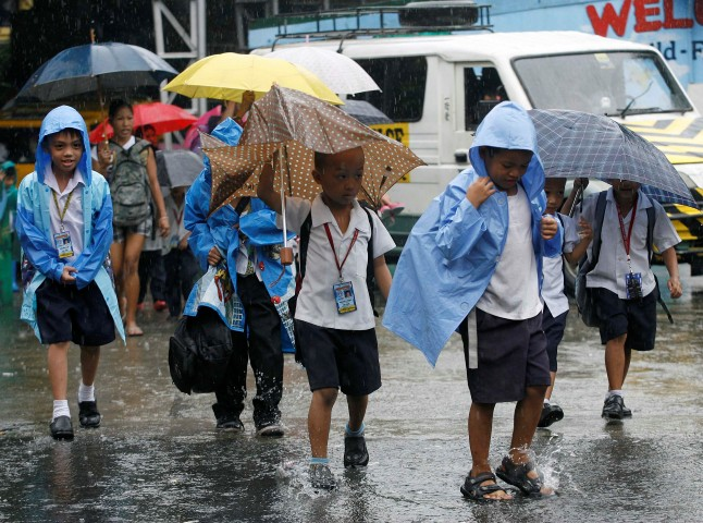 Students walk home in the rain after the suspension of classes due to rainfall from Typhoon Nesat in Quezon City, Metro Manila September 26, 2011. The Department of Education suspended afternoon classes in the preschool, elementary and high school levels of both private and public schools in Metro Manila due to Typhoon Nesat, which is locally known as Tropical storm Pedring, according to local media reports. REUTERS/Cheryl Ravelo (PHILIPPINES - Tags: SOCIETY ENVIRONMENT)